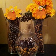 Thanksgiving centerpieces without candles. I used acorns, pinecones, straw, artificial flowers & leaves, scrapbook paper turkey bodies in glass vases