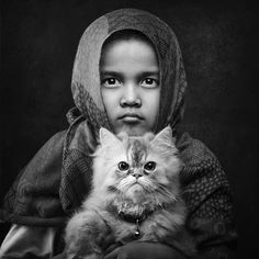 The photographer of this portrait is Arief Siswandhono, and the girl in the picture is her daughter, Fina. Fina was once terrified of cats, but after her parents adopted 2 kittens her life was changed. Fina now considers the cats her best friends.