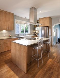 cooking island with floating vent hood; white oak cabinetry and flooring