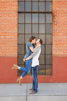 Fall Engagement Session - Fiancé - Man - Woman - Billings - Downtown - Kissing - Lifting - Foot Popped - Brick Building - Sidewalk - Window - Orange - Red - Outdoor - Glasses - White and Gray Shirt - Jeans - Brown Boots - Blue Shirt - Montana Wedding Photographer - Sara Nagel Photography