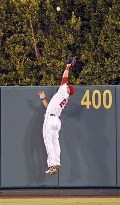 Trout brings one back: Mike Trout leaps high over the outfield wall for an amazing catch, robbing yet another home run in breathtaking fashion on August 12, 2012 - AP Photo/Reed Saxon