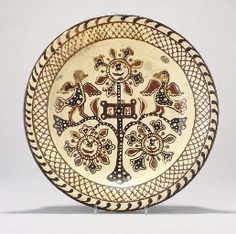 A STAFFORDSHIRE SLIPWARE CHARGER  19TH CENTURY  Centre by the intials S.M. within a flowering tree with stylised birds and lattice-work borders (cracked, chipped, and restored)  15¾ in. (40 cm.) diam.