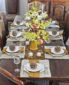 The combination of leaves, pinecones and tree branches looks great on the dark brown table