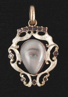 "Hazel eye miniature hand-painted on ivory, set in 18K yellow gold under rock crystal, elaborate white enamel surround with ""A Token of Love"" on surround, c 1780, woven hair in back. Heart-shape is typical of eyes painted during this time frame."