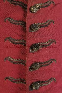 """Detail emboirdery, waistcoat, England, c. 1755. Crimson silk faille, buttonholes embroidered with silver thread in a """"flame"""" design and buttons laid with crossed silver thread, back of wool."""