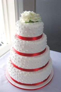 http://www.simmer.co.nz/Wedding%20Cakes/White%203%20Tier%20Wedding%20Cake%20with%20mini%20white%20flowers%20and%20red%20ribbon.jpg