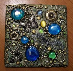 "Garden tile by Christina A Kapono. Polymer clay on a 6"" square piece of treated hardboard. Included are brass butterfly, leaves and flowers, glass gems and a metal dragonfly. Painted with acrylic and metallic paint."