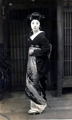 Geisha holding her kimono 1930s    This is a photograph of a beautiful Geisha standing outside of an Okiya or Geisha House. The decoration on her kimono appears to show a woman travelling in a Kago or Palanquin, carried by bearers.