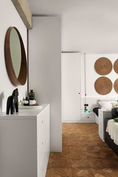 Most of the necessary storage space is housed in minimalistic white drawers treated with a silky white finish - it looks clean and sharp, and most importantly, doesn't take any emphasis away from the more important decorative details throughout the apartment. Using round decor provides an interesting contrast to the cubic forms of the furniture.