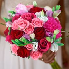 Ce bouquet de mariée se compose de lisianthus blancs, roses branchues roses, roses rouges, oeillet fuchsias et freesias roses.