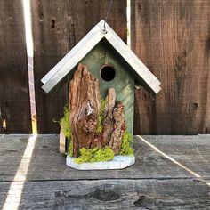 Rustic birdhouse Ive handcrafted from scratch, then painted the color of Moss Green. Ive attached driftwood sticks and tucked moss all around. The roof is painted White over Grey. Birdhouse is functional with clean out door on the side. Hangs with 18-gauge wire attached with