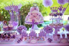 """A pequenina Camila fez 4 anos. E como adora a Princesa Sofia, inspirámo-nos nela e criámos uma festa à altura de uma verdadeira princesinha. O Clube de Ténis, em Carcavelos, foi o cenário ideal para montar este verdadeiro conto de fadas que todos adorararam. A decoração, em tons de alfazema e rosa, incluia as mais irresistíveis guloseimas, sob várias formas: um bolo """"Vestido de Princesa"""", um armário com vestidos em Bolacha, e sapatos de cristal recheados com doces. E ainda: Coroas, chapéus…"""