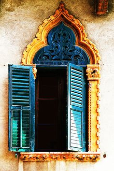 amazing window framed in canary yellow.  shutters are blue with green.  above them, still in the frame, is an intricate blue wood carving.