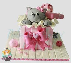 The Kitty - The kitty…  Once upon a time, there was a little girl who dreams she has a kitty. Out of a sudden, a mysterious beautiful box appears. What could be inside? Wow!! A beautiful kitty!!! This cake was made for a local magazine. All cake is edible. Cat hand moulded with sugar paste and cake covered with sugar paste.