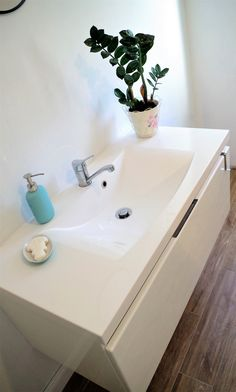 white sink, white bathroom, bathroom with greenery