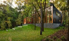 Dark standing seam metal siding on the side transitions to full height glazing in a wood structure...