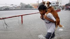 A boy carries his dog in through flood waters in Paranaque city in the Philippines. (© Romeo Ranoco/Reuters)