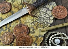 stock-photo-pirate-still-life-with-decorated-dagger-map-ancient-coins-and-pearl-necklace-on-wooden-background-256245451.jpg (450×327)
