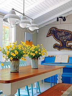 When rustic charm is your design goal, try a farmhouse lighting fixture with galvanized steel shades and metal lamp guards reminiscent of those used in 1930s-era barns. In this dining room, the pristine white walls, ceiling, and beams balance the primitive vibe of the fixture.