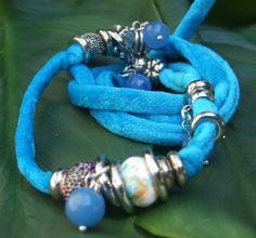 Bracciale in lycra azzurra. Charms in resina sintetica e charms in metallo color argento, con pendenti in cristallo azzurro