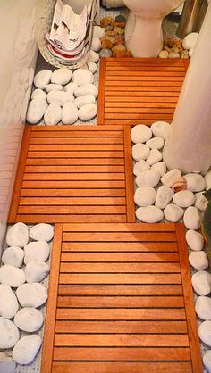 Great idea to make an ugly bathroom floor pretty.  I think I would use darker stones though.