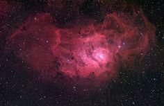 A Nebulosa da Lagoa, ou M8 (NGC 6523). É uma nebulosa de emissão que contém um enxame estelar à sua frente e várias regiões de formação estelar. O brilho vermelho é hidrogénio.