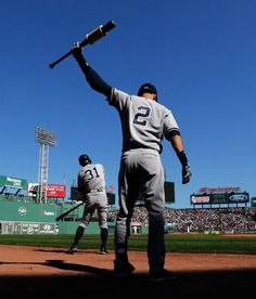 New York Yankees designated hitter Derek Jeter loosens up in the on-deck circle as he prepares to face Boston Red Sox starting pitcher Joe Kelly in the first inning of a baseball game at Fenway Park in Boston, Saturday, Sept. 27, 2014. At left is lead off hitter Ichiro Suzuki. (AP Photo/Charles Krupa)
