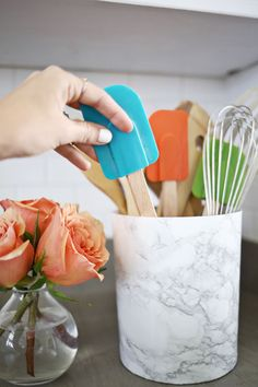 Try this! Re-cover your utensil holder with marble contact paper for a inexpensive marble look.
