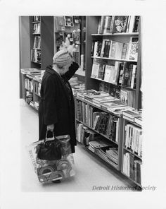 Black and white photographic print of a woman viewing craft and game publications available for purchase at the Doubleday Bookstore; the woman, dressed in her winter coat and hat, holds a Hudson's Budget Store shopping bag. Dated 12/1973