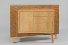 Intersections Table by Todd Leback. Shown in ropey cherry and bird's-eye maple, the Intersections table is inspired by the large slabs and surfaces of Brutalist architecture. Made of ultra-flat and stable mdf and veneered in the highest quality woods, the large wedge of the table is interrupted by a contrasting storage cabinet containing three drawers and shelf space. The table is finished with a tough, durable pre-catalyzed lacquer and hand-rubbed with wax and steel wool to bring it to a…
