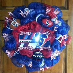 Houston Texans wreath! Navy and red deco mesh, red and white glitter ribbon, red waffle ribbon, white and red flex tubing, 3 Texans mini footballs, and Texans license plate in the center.