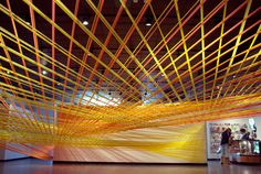 Straddle the line, in discord and rhyme (2009) by Megan Geckler. Flagging tape, eye hooks and existing architecture.