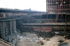 Construction view of the original World Trade Center with the North Tower and the still-open West Side Highway in the background. Looks like the PATH train tube is exposed across the worksite. New York. 1967. by wavz13 on Flickr.