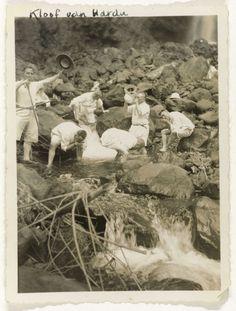 Anonymous   Kloof van Harau, Anonymous, 1930 - 1939   Zes Fraters van Tilburg in korte broek, poseren hurkend en drinkend uit een stroom bij de waterval in de kloof van Harau op Sumatra. Losse foto afkomstig uit het losbladig fotoalbum over de Fraters van Tilburg op Celebes en Sumatra.