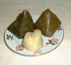 Num kom s'det khieu.  (Sticky rice cake with mung bean.)  The Pyramid shape cakes are a religious symbol representing the Buddhist pagoda towers, where souls emerge from the top on their path to reincarnation. Traditionally, on Memorial day for ancestors ( Pchum ben/Don-ta), Visak( Buddha birthday) and especially Cambodian New Year(Bon chol thnam thmey), Khmer Krom villagers at my village would make or buy *num kom* for food offerings.