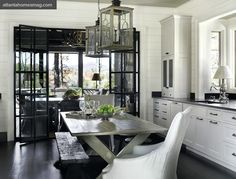 source: Atlanta Homes & Lifestyles  Nancy Warren - Stunning kitchen design with creamy white shaker kitchen cabinets, glass folding doors opening into deck patio, gray painted dining table, rustic wood bench, industrial stools, white clip-covered chairs, and lanterns.