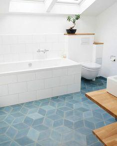 nuance de bleu gris sur le carrelage d'une salle de bains sous pente aux meubles blancs avec baignoire revêtue en carrelage blanc