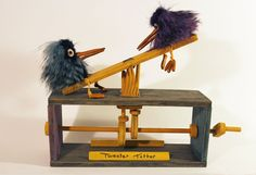 Two fluffy birds move up and down on a teeter totter, their beaks snapping open and closed. Watch it working!-->www.youtube.com/watch?v=5SEr8D… Cam automaton made from wood, faux fur, pol...