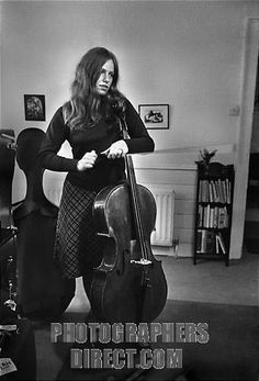 Jacqueline Du Pre standing , holding cello in apartment she shared with Daniel Barenboim, London, England, 1968