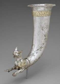 ancientpeoples:  Silver and mercury rhyton ending in the form of a wild cat  There is a spout pouring from the middle of the cat's chest. There are also dionysiac symbols on the cat; grapevines are symbolic for this god. The Parthian culture absorbed these images from the Greek culture.  Parthian  Found in Iran  Source: The Metropolitan Musem