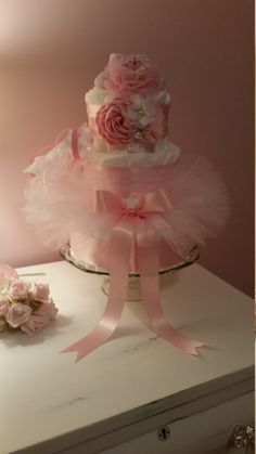 NOTE: (Due to limited supplies of unique craft items the style headband and booties/socks design will vary but always compliment your cake.) This gorgeous cake is the perfect centerpiece for your babys room or shower table-scape. You will receive:  -One 3 Tier Diaper Cake approximately/ 65 diapers in your choice of Pampers Swaddlers Size 2 or Babyganics Organic Disposable Diapers Size 3. -Top Tier has a Tiara Clip on Pink Tulle Pom Pom, and Baby Booties Size 0-to 12 months behind (style will…