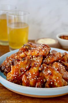 Crispy Baked Orange Chicken Wings on pale blue plate with two glasses of beer in background.