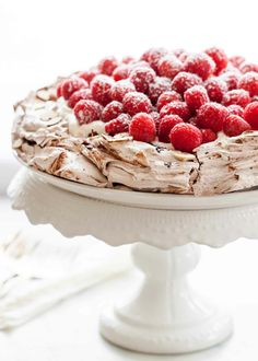 This chocolate pavlova topped with whipped cream and raspberries is a show-stopper, for sure. It also happens to be easy to make! If you can make meringue, you can make this. #pavlova #meringue #DinnerParty #desserts #HolidayParty
