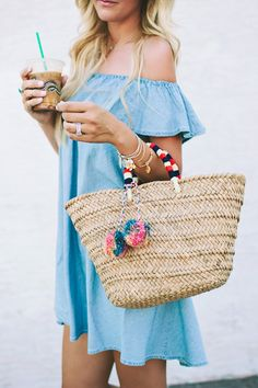 Denim Ruffle Dress, a woven tote with pom poms, and leather sandals