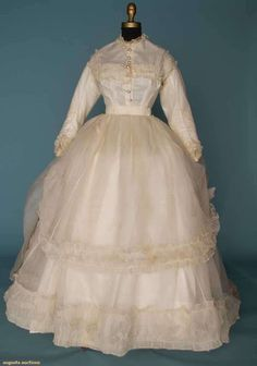 1860s white organdy wedding dress, 2-piece, both trimmed w/self ruffles: 1-piece Polonaise dress and trained underskirt w/white cambric petticoat.  Via Augusta Auctions.