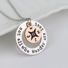 "The perfect gift for a traveler, graduate or dreamer. This hand-stamped disc with Tolkien inspired quote ""Not All who wander are lost"" also includes a cute little compass charm and both hang from an 1"