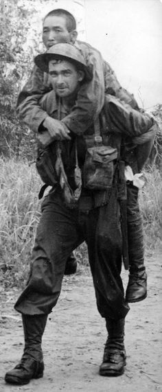 [Japanese soldiers, now prisoners of war] Wounded Japanese soldier being carried by unidentified Allied soldier.