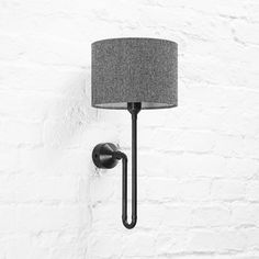 Industrial design wall light in modern white brick apartment. Simple, yet very characteristic sconce for urban loft interiors. Here shown in black patina metal finish, with herringbone shade. Loft Interiors, Colorful Interiors, Brass Sconce, Sconces, Loft Wall, Patina Metal, Urban Loft, Bedside Lamp, Metal Finishes