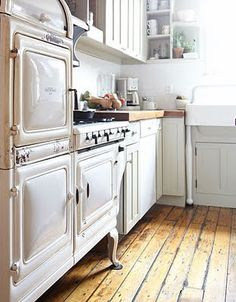 my ideal stove, here seen in such a unique shape. adore the butcher block countertops, the aged wood floors, and those precariously stacked white teacups in the back.