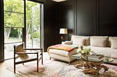 Dark walls paired with light furnishings and a generous window make for a warm living space